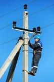 Instalador de líneas del electricista de la potencia en el trabajo sobre poste Imagen de archivo