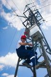 Instalador de líneas del electricista de la potencia en el trabajo sobre poste Fotografía de archivo libre de regalías