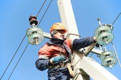 Instalador de líneas del electricista del poder en el trabajo sobre polo Imagen de archivo libre de regalías