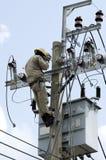 Instalador de líneas del electricista en el trabajo que sube sobre polo de la corriente eléctrica Imagen de archivo