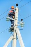 Instalador de líneas del electricista de la potencia en el trabajo sobre poste Imagen de archivo libre de regalías