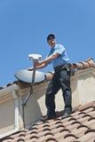 Instalador por satélite en el tejado imágenes de archivo libres de regalías