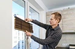 Instalando cortinas de madeira imagem de stock