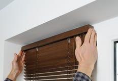 Instalando cortinas de madeira imagens de stock