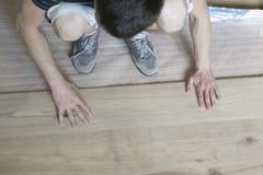 Instalando el suelo laminado que cabe el pedazo siguiente - céntrese en h foto de archivo