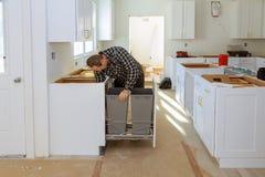 Instalando o hob novo da indução na instalação moderna da cozinha do escaninho de lixo das gavetas imagens de stock