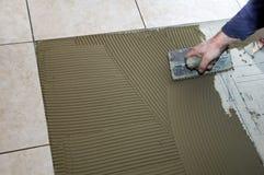 Instalando a telha cerâmica Fotos de Stock