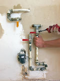 Instalator at work. Close up of the hands of instalator mounting water valves in the plumbing installation royalty free stock image
