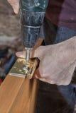 Instale as dobradiças para a porta interior de madeira, parafuso de parafusamento do marceneiro fotos de stock