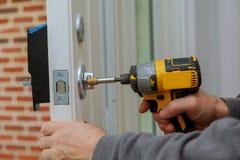 Instale el tirador de puerta con una cerradura, carpintero aprietan el tornillo, usando un destornillador del taladro eléctrico, Fotos de archivo