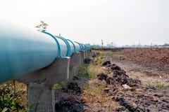 Instale tubos el tubo del abastecimiento de agua a la utilidad con los polos concretos, tubo de agua azul en polos concretos, imagen de archivo