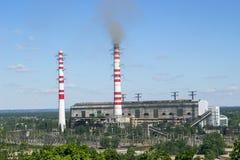 Instale tubos la planta industrial con humo contra el cielo azul brillante y sobre árboles verdes imagen de archivo libre de regalías