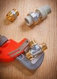 Instale tubos los accesorios y la llave inglesa en cierre del tablero de madera para arriba Foto de archivo