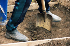 Install the formwork and remove the top layer of the ground by digging a pit or trench. Independent concreting of the site or trac. K. A man in dirty shoes is Stock Images