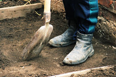 Install the formwork and remove the top layer of the ground by digging a pit or trench. Independent concreting of the site or trac. K. A man in dirty shoes is Royalty Free Stock Photo