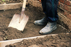 Install the formwork and remove the top layer of the ground by digging a pit or trench. Independent concreting of the site or trac. K. A man in dirty shoes is Stock Photography