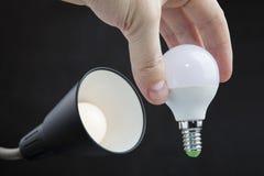 Install LED light bulb in lamp shade home light fixture. Stock Image