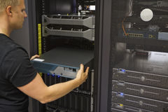 Install Network Router. It engineer / consultant install / inserts a router / switch in a rack. Shot in a data center Stock Photo