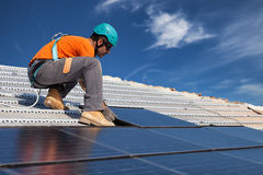 Install solar panels. Technician install new generation photovoltaic solar panels on roof Royalty Free Stock Images