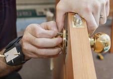 Installando la porta interna, il carpentiere installa la manopola facendo uso di magnetico fotografia stock