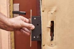 Installant une nouvelle serrure sur la vieille fin de porte  image libre de droits