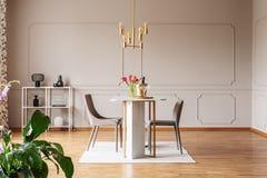 Installatie dichtbij stoelen bij lijst met bloemen in modern grijs eetkamerbinnenland met gouden lamp Echte foto stock foto