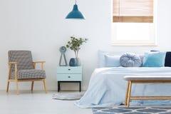 Installatie op kabinet tussen gevormde leunstoel en blauw bed in bedr royalty-vrije stock afbeeldingen