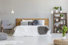 Installatie op poef in helder slaapkamerbinnenland met houten bed naast gevormde leunstoel Echte foto royalty-vrije stock afbeeldingen