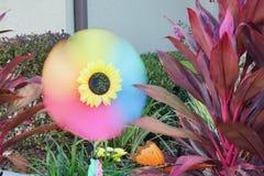 Installatie van de Cordyline de Rode Zuster en Spinnende kleurrijke pastic de windmolen van de zonbloem in een tuin Royalty-vrije Stock Fotografie