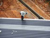Installatie van het dakblad van het metaaldek door bouwvakkers royalty-vrije stock afbeeldingen