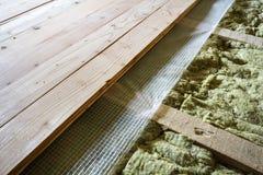 Installatie van nieuwe vloer van houten natuurlijke planken en steenwolisolatie voor isolatie en het houden van warmte Moderne te royalty-vrije stock afbeeldingen