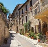 Installaties en bloemen in potten op smalle straten van het oude dorp van Spello, Umbrië, Italië Stock Fotografie