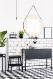 Installaties en spiegel in zwart-wit badkamersbinnenland met geruite vloer en kruk Echte foto royalty-vrije stock afbeeldingen