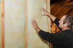 Installation av inre väggisolering i trähus som bygger under konstruktion fotografering för bildbyråer