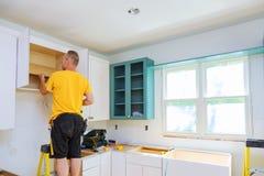 Installation av kök Arbetaren installerar dörrar till köksskåpet arkivfoton