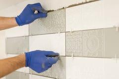 Installation av keramiska tegelplattor på väggen i kök Förlägga tegelplattaavståndsmätare med händer, renovering, reparation, kon royaltyfri foto