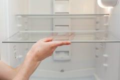 Installation av nya rena hyllor i ett tomt tvättat kylskåp Lokalvårdkylskåp för ung kvinna royaltyfri fotografi