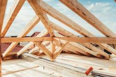 Installation av trästrålar på huskonstruktionsplatsen Byggande detaljer med trä-, timmer- och järnhållare royaltyfri bild