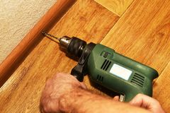 Installation of baseboards with a drill. Instruction royalty free stock images