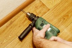 Installation of baseboards with a drill. Instruction stock photos
