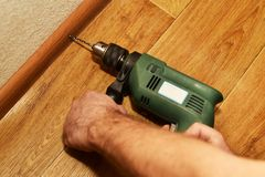 Installation of baseboards with a drill. Instruction stock images