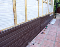 Installation of brown plastic siding on the facade Stock Photography