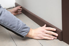 Installation of a brown wooden baseboard Royalty Free Stock Images