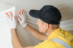Installation of ceiling moldings. Worker fixes the plastic molding to the ceiling royalty free stock photos