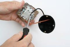 Installation d'un interrupteur de lampe dans une prise murale Photographie stock libre de droits