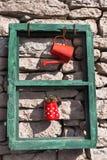 Installation d'un vieux châssis de fenêtre, boîte d'arrosage et cruche avec une usine sur un mur en pierre un jour ensoleillé photos libres de droits