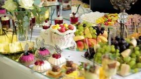 Installation de décoration de friandise de mariage avec les gâteaux et les bonbons délicieux banque de vidéos