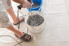 Installation de système électrique de chauffage par le sol dans la nouvelle maison Mélangeur concret de main d'utilisation de tra Photos libres de droits