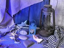 Installation of decorative lantern, sea stones, seashells, paper boats, sea salt on a wooden table, textural background stock images