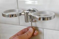 Installation des Becherhalters im Badezimmer das Konzept der Anordnung und Reparatur des Wohnraums stockfoto